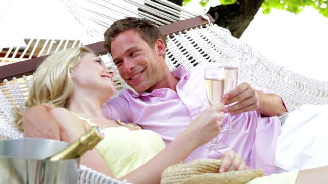 paar entspannung in der hängematte am strand trinken champagner - champagner toasts stock-videos und b-roll-filmmaterial