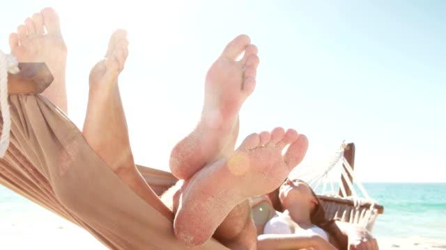 coppia rilassante in amaca sulla spiaggia - amaca video stock e b–roll