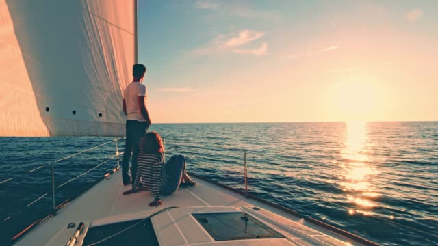 WS Couple relaxing on a deck of a sailboat at sunset