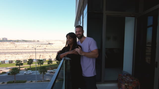 Couple relaxing on the balcony of their home in Dubai - video
