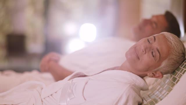 couple relaxing on warm tepidarium at the spa - zabieg spa filmów i materiałów b-roll