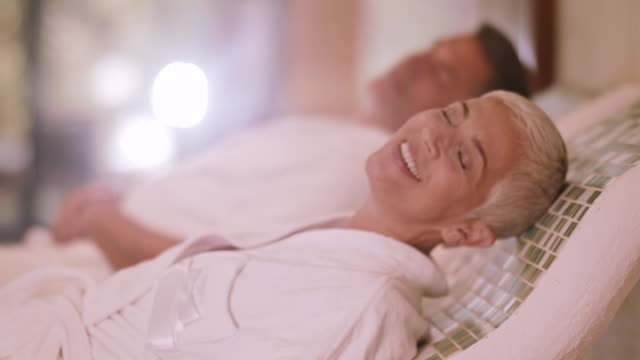 Couple relaxing on warm tepidarium at the spa