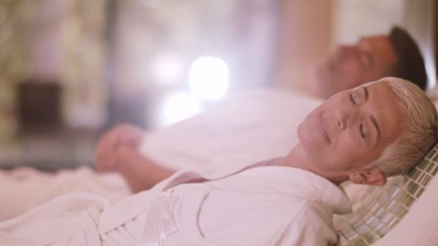 vidéos et rushes de couple de détente sur chaud tepidarium au spa - peignoir