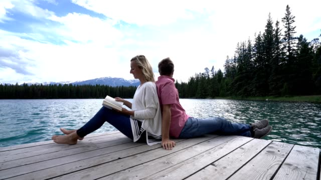 Couple relaxing on wooden lake pier, sitting back to back, Canada Cheerful young couple sitting back to back on wooden laker pier at Maligne lake in Jasper national park, Canada. People travel relaxation love concept back to back stock videos & royalty-free footage