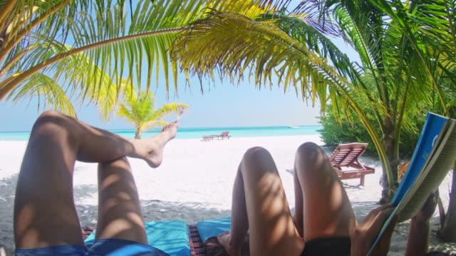 ms couple unter palmen entspannen, lesen auf idyllischen tropischen strand, malediven - sun chair stock-videos und b-roll-filmmaterial