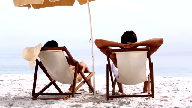 Couple relaxing under parasol video