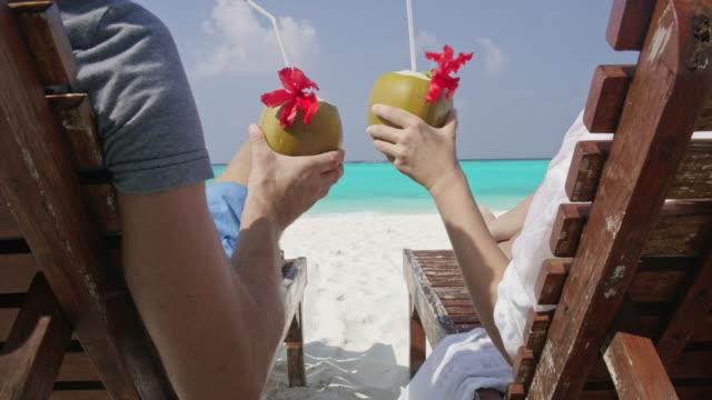 ms couple avkopplande, rosta kokos drycker på solstolar på solig tropisk ocean beach, maldiverna - indiska oceanen bildbanksvideor och videomaterial från bakom kulisserna