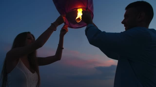 Couple Releasing Sky Lantern Tilt up of loving couple releasing Chinese lantern into sky on romantic date on beach at dusk boyfriend stock videos & royalty-free footage