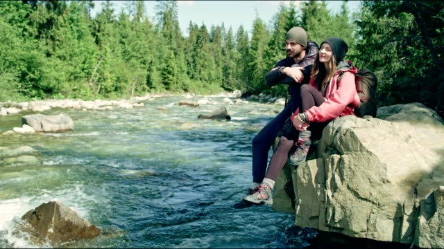 vídeos de stock e filmes b-roll de couple resting on a rock above river - man admires forest