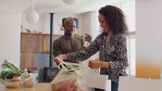 カップルは買い物旅行から家に帰るプラスチックの無料の食料品の袋を解凍 - 荷物をとく点の映像素材/bロール