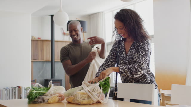 couple returning home from shopping trip unpacking plastic free grocery bags - portare video stock e b–roll