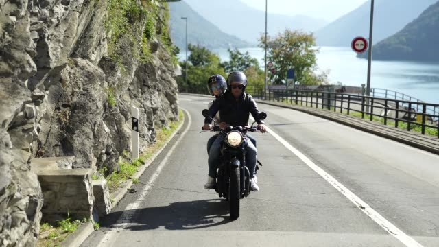 Couple riding a motorcycle on a road near a lake Details of people enjoying a lakeside on a sunny day crash helmet stock videos & royalty-free footage