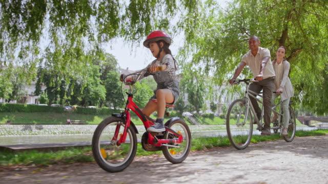 vídeos y material grabado en eventos de stock de slo mo ts pareja montando una bicicleta en tándem y su hija pequeña está montando a su lado a través del parque - grupo multiétnico