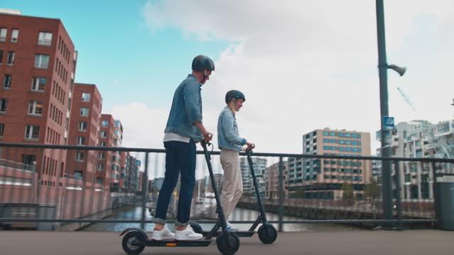couple riding electric push scooters on bridge - monopattino elettrico video stock e b–roll