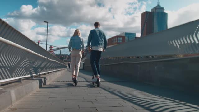couple riding electric push scooters on footbridge - monopattino elettrico video stock e b–roll