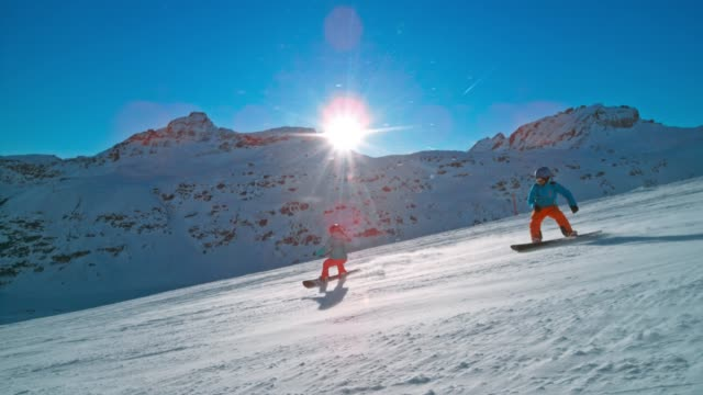 slo mo ts couple riding snowboards down the sunny mountain slope - snowboarding video stock e b–roll