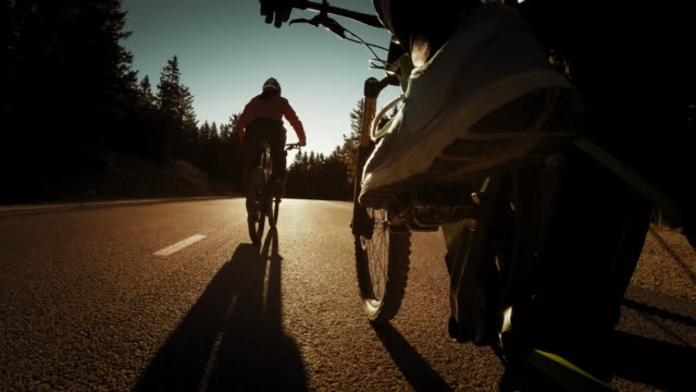 POV Couple riding their bikes on a country road at sunset video