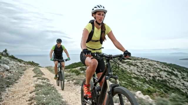 couple riding their bikes up a mountain at the seaside on a cloudy day - andare in mountain bike video stock e b–roll