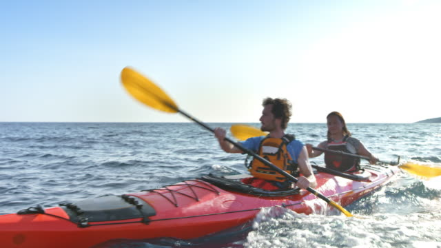 Couple riding their kayak at sea in sunshine Wide handheld shot of a man and a woman sitting in a red sea kayak and paddling in sunshine. Shot in Slovenia. human relationship stock videos & royalty-free footage