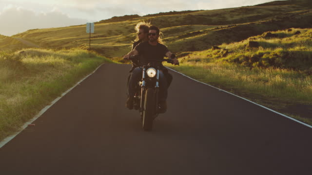 Couple Riding Vintage Motorcycle Couple riding vintage motorcycle on country road at sunset motorcycle stock videos & royalty-free footage