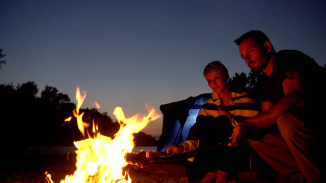 HD CRANE: Couple Roasting Meat On Campfire