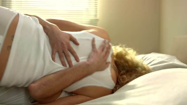 Couple Rolling Around On The Bed