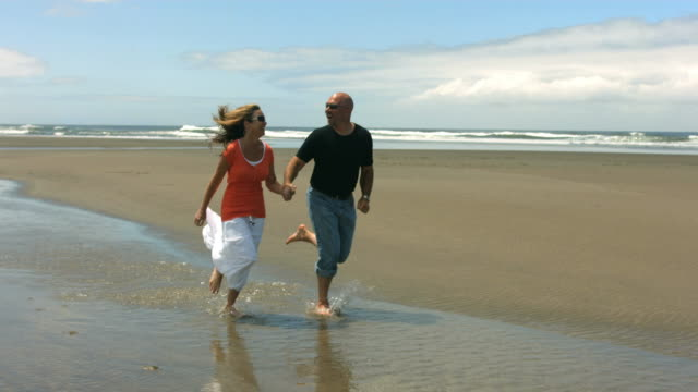 Couple run on beach together, slow motion speed ramp video