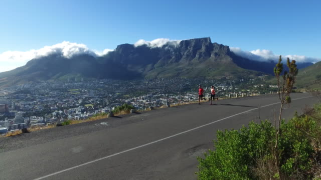 Couple running along a road overlooking Table Mountain A fit young couple enjoy running on the road with a view over Table Mountain in Cape Town table mountain national park stock videos & royalty-free footage