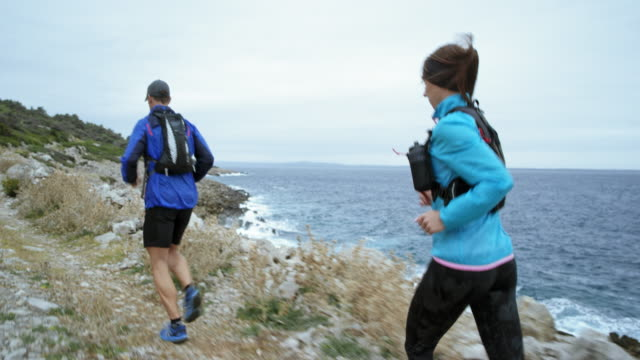 Couple running along a rugged beach on a rocky trail in bad weather video
