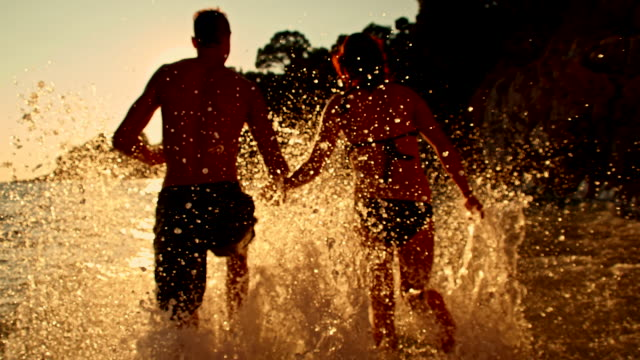 SLO MO Couple Running Into The Sea video