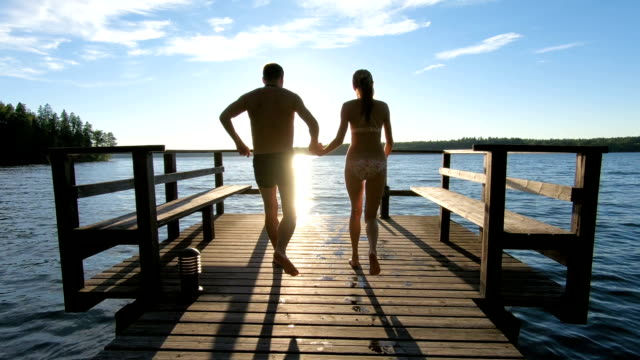 couple running on a wooden pier and jumping into the lake