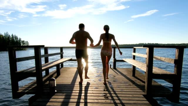 par som springer på en träbrygga och hoppar in i sjön - flod vatten brygga bildbanksvideor och videomaterial från bakom kulisserna
