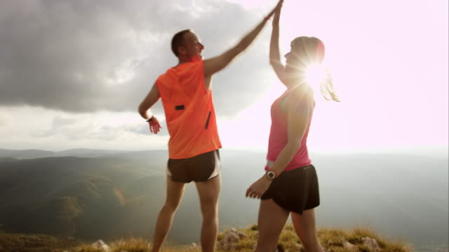 TS couple running to the top and raising hands Medium tracking shot of couple running to the edge of the mountain top. They stop and the woman raises her hands into the sun while the man is showing her from where they started in the valley bellow. top garment stock videos & royalty-free footage