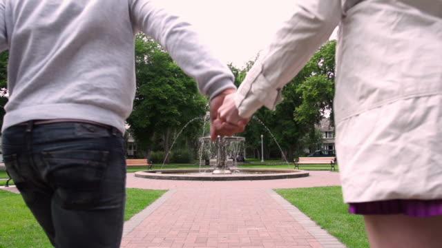 Couple running toward fountain video