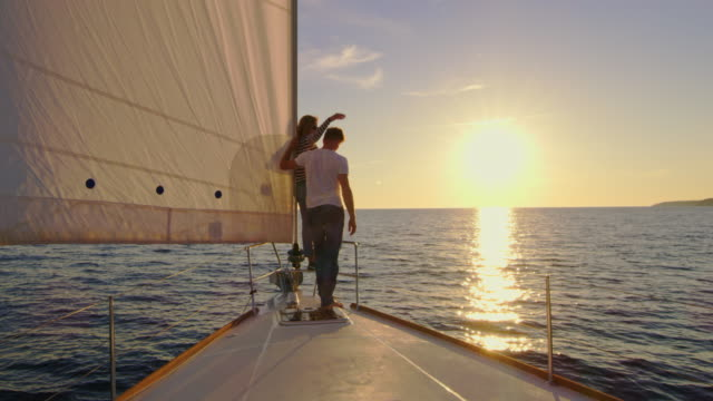 vídeos de stock e filmes b-roll de slo mo couple sailing at sunset - veleiro