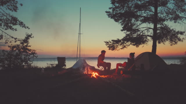 couple, sailing boat and bonfire. young couple sit near the bonfire with sailing boat beached on the background - дикая растительность стоковые видео и кадры b-roll