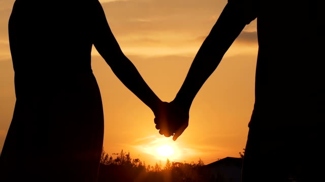 couple separating their hands at sunset, love story ending, family break-up - dividere video stock e b–roll