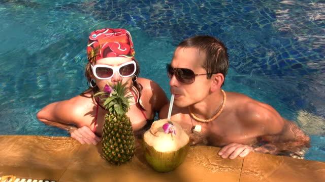 vídeos de stock e filmes b-roll de casal partilha cocktails - mulher natureza flores e piscina