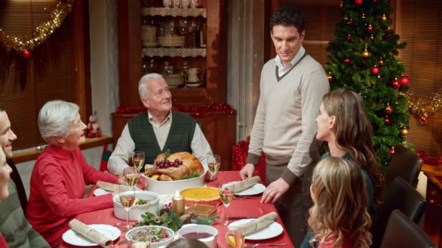 幸せなカップルの共有テーブルニュースのクリスマスに家族 - 親族会点の映像素材/bロール