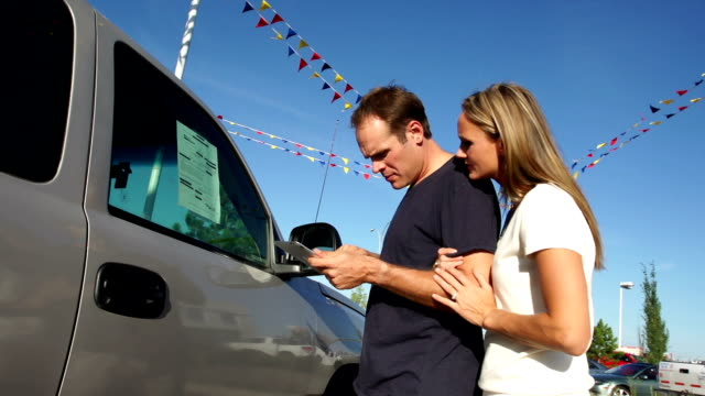 Couple shop for a vehicle Couple shop for a new vehicle using a tablet. mid adult stock videos & royalty-free footage