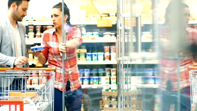 Couple shopping in supermarket. Closeup of early 30's couple doing some home shopping in local supermarket. They are walking down aisles and picking up some food items. Side view. freezer stock videos & royalty-free footage