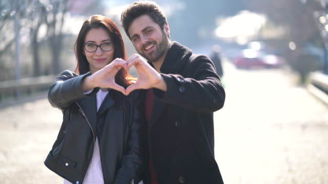 Couple showing heart shape symbol with hands