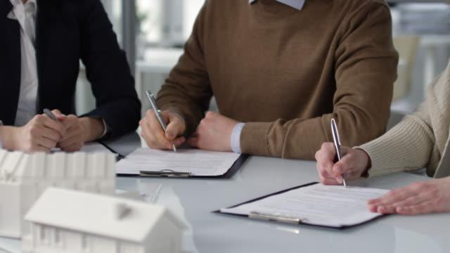 vidéos et rushes de couples signant des papiers d'hypothèque pour la première maison - notaire