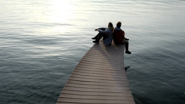 vídeos de stock e filmes b-roll de couple sit and enjoy atmospheric lake dock admiring tranquil mountain view - lago maggiore