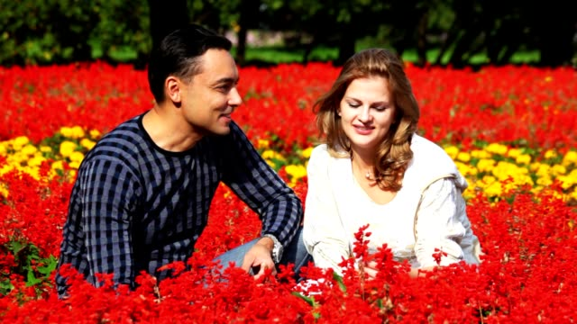 Couple sit in park, smell flowers and smile video