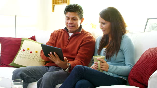 Couple sit together using tablet computer video