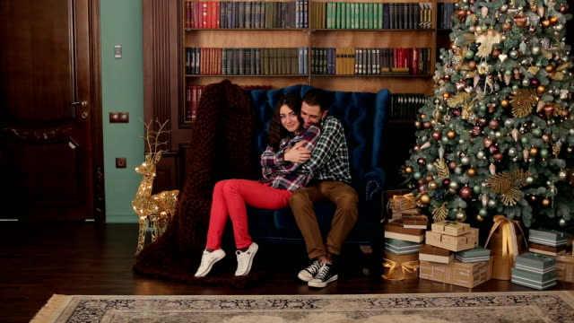 Couple sits embracing near Christmas tree at home. video