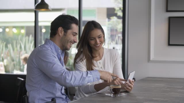 커플 앉아서 스마트폰 사진을 보고 - 방관적인 사람들 스톡 비디오 및 b-롤 화면