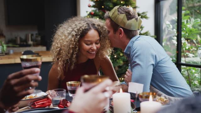 coppia seduta intorno al tavolo da pranzo a casa per la cena di natale con gli amici che parlano e sussurrano - pranzo di natale video stock e b–roll