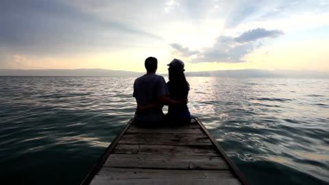 vidéos et rushes de couple assis sur la plage - jeune couple